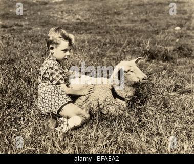 Boy Holding Lamb in Pasture - Stock Photo