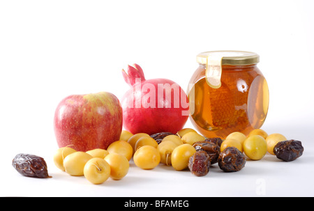 Apples, Honey, pomegranate, and dates, Symbols of Roah Hashanah the Jewish New Year on white background - Stock Photo