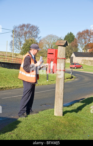 Postman collecting letters from a rural post box near Reeth, Swaledale. - Stock Photo