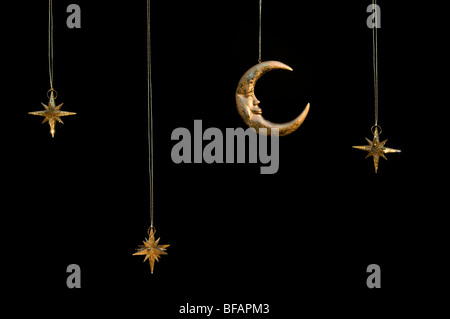 Gold shiny moon and stars sparkly hanging christmas decorations against a black background - Stock Photo