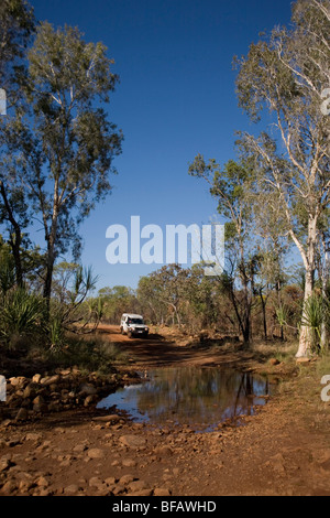 Camper van crossing creek on the Gibb River Road – former drovers track through the Kimberley in Western Australia - Stock Photo