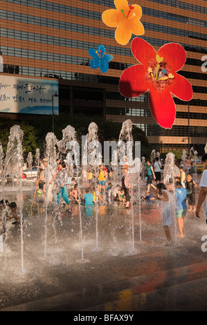 Children playing in the fountains at Gwanghwamun Plaza in Seoul, South Korea. - Stock Photo