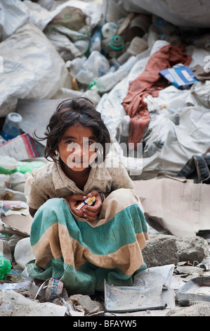 Young Indian lower caste street girl sitting amongst rubbish dump that is being sorted for recycling. Andhra Pradesh, - Stock Photo