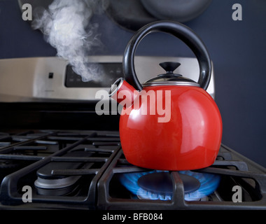 A red teapot is on the boil and steam is pouring out of the spout. - Stock Photo