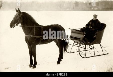 Man Driving Horse Drawn Sleigh at Edge of Frozen Lake - Stock Photo