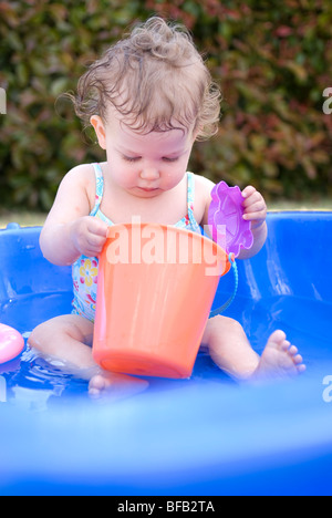Sixteen month old girl playing in small back garden paddling pool. - Stock Photo