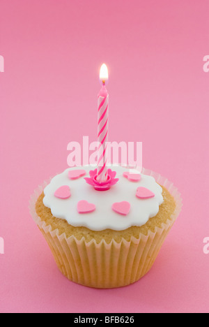 Single cupcake with lit candle - Stock Photo