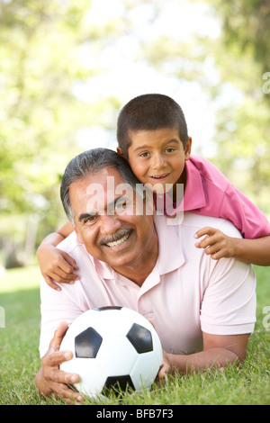 Grandfather With Grandson In Park With Football - Stock Photo