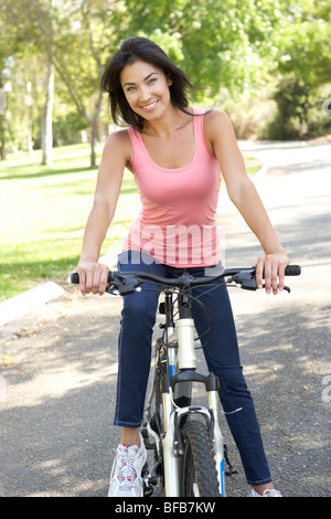 Young Woman Riding Bike In Park - Stock Photo