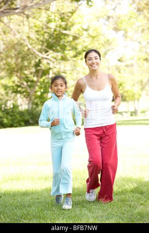 Mother And Daughter Exercising In Park - Stock Photo