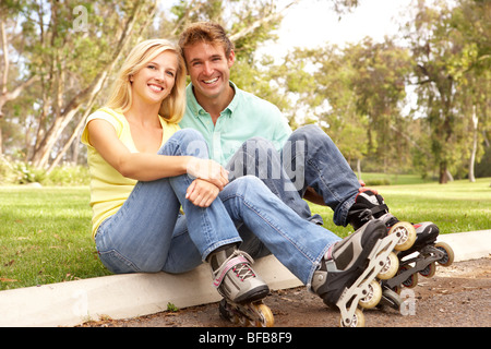 Couple Putting On In Line Skates In Park - Stock Photo