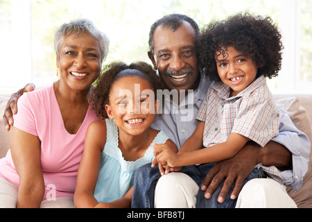 Grandparents With Grandchildren Relaxing On Sofa At Home Together - Stock Photo