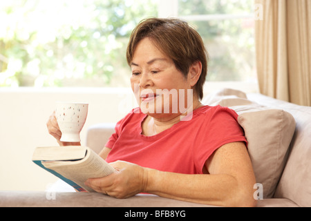 Senior Woman Reading Book With Drink At Home - Stock Photo