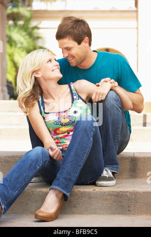 Young Couple Sitting On Steps Of Building - Stock Photo