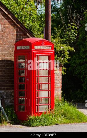 Red telephone box in summer sun - Stock Photo