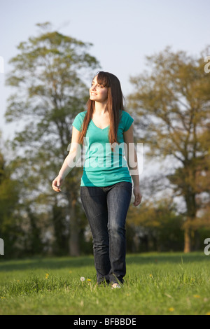 Teenage Girl Walking Through Summer Meadow - Stock Photo