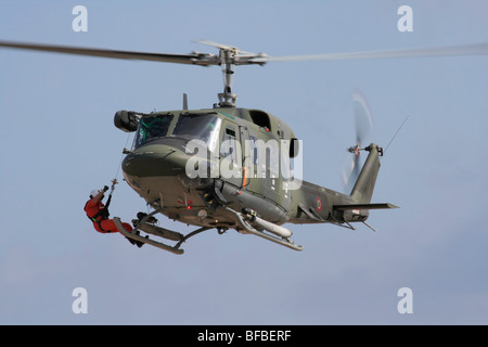Italian Air Force AB212 helicopter hovering and performing a rescue simulation - Stock Photo