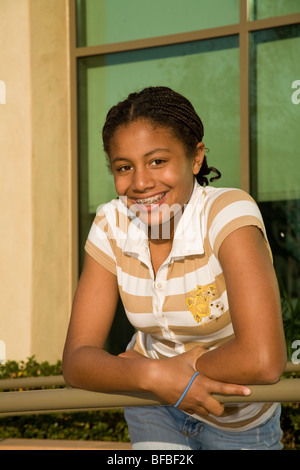 African American/Caucasian girl with braids 13-14 year old happily smiling and posing for camera. MR - Stock Photo