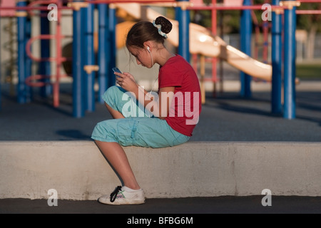 11 year-old girl plays an electronic game on her iPod Touch in the playground of a neighborhood school in San Jose, - Stock Photo