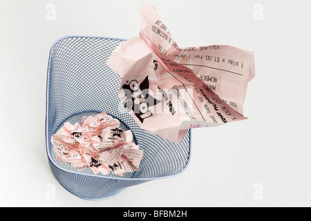 composite image of screwed up unlucky Lotto UK National lottery ticket thrown into a waste paper basket to illustrate - Stock Photo