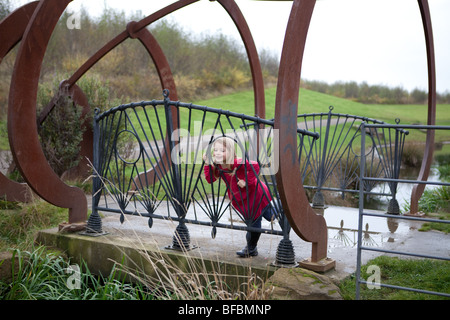 6 year old girl in a pink winter jacket on a concrete bridge with iron rails and rusted steel decoration set in - Stock Photo