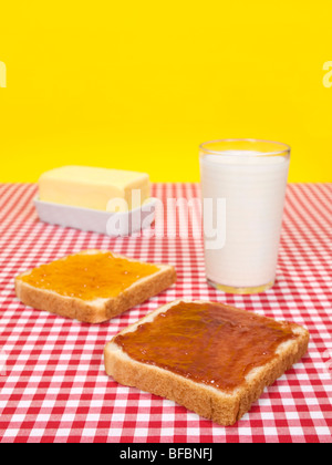 Two slices of bread spread with jam, a glass of milk and a butter stick. - Stock Photo