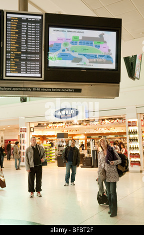 Travellers looking at the departures board in terminal One departure lounge, Heathrow airport, London, UK - Stock Photo