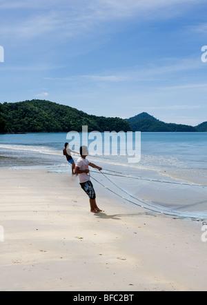 Two Malaysian fishermen hauling in a net on Pantai Tengah beach in Langkawi, Malaysia. - Stock Photo