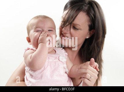 Brunette mum plays with blonde baby daughter on white background. twenty something mum and one year old little girl - Stock Photo