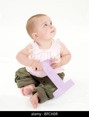 Baby Girl plays with Big Letter in Pink Top and Green Trousers - Stock Photo