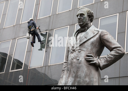Statue of George Stephenson outside Euston station, London, with a window cleaner at work - Stock Photo