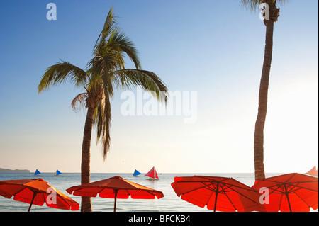 Red parasols and sail boats Boracay; The Visayas; Philippines. - Stock Photo