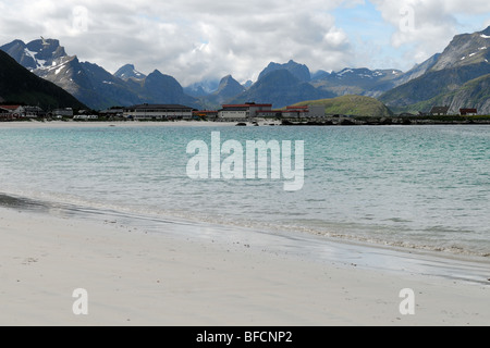 A beautiful beach with white sand and azure water surrounded by the mountains on the Lofoten Islands. - Stock Photo
