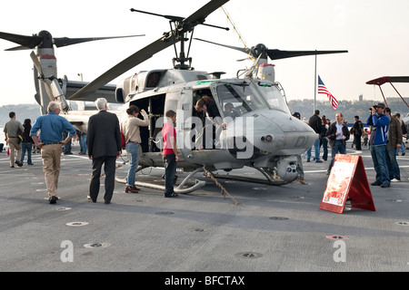 visitors admire a Marine Corps Huey helicopter sitting on the flight deck of the USS New York as woman clambers - Stock Photo