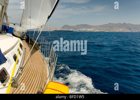 Yacht on port tack, heeled over,  sailing up Bodrum / Kos Channel. Bodrum Peninsula and a tanker in the horizon - Stock Photo