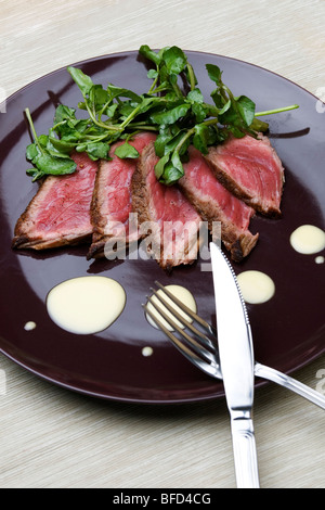 Slices of beef with orange mayonaise sauce on the side - Stock Photo