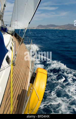 Yacht on port tack, heeled over,  sailing up Bodrum / Kos Channel. Bodrum peninsula in the horizon. Sunny day with - Stock Photo
