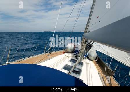 Yacht on port tack, heeled over,  sailing up Bodrum / Kos Channel. A tanker approaching on the horizon. Sunny day - Stock Photo