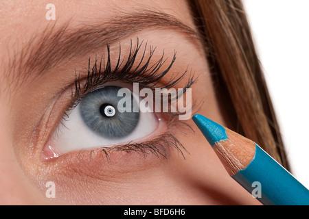 Close-up of blue eye, woman applying blue make-up pencil, macro lens - Stock Photo