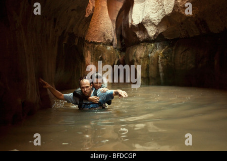 A couple wades through a cold pool in a slot canyon in Utah. - Stock Photo