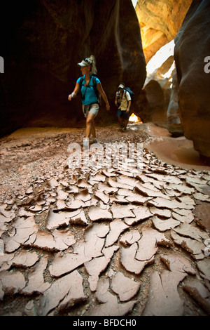 A man and woman hiking through a narrow canyon past dried and cracked mud in Utah. - Stock Photo