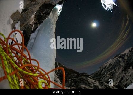 Night view of ropes as a young man ice climbs with a headlamp under a full moon. - Stock Photo