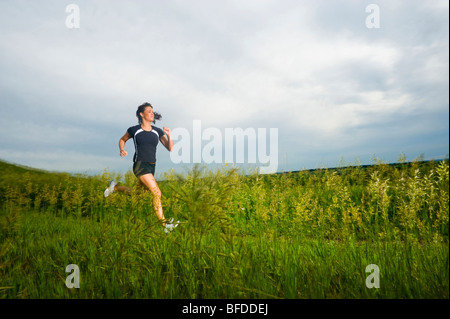 Young woman running on grass trail through a bright green field at Spirit Mound, South Dakota. - Stock Photo