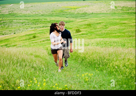 Young couple running up a hill through a bright green field at Spirit Mound, South Dakota. - Stock Photo