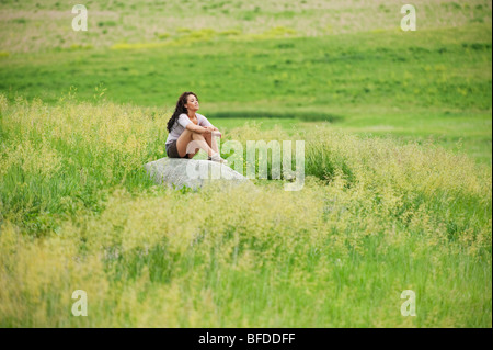 Young woman siting on rock in a bright green field at Spirit Mound, South Dakota. - Stock Photo