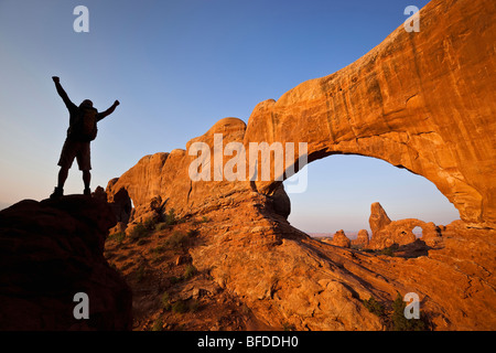 A silhouetted hiker raises his arms beside an arch in Arches National Park, Utah. - Stock Photo