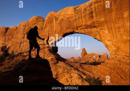 A silhouetted hiker stands looking at an arch in Arches National Park, Utah. - Stock Photo