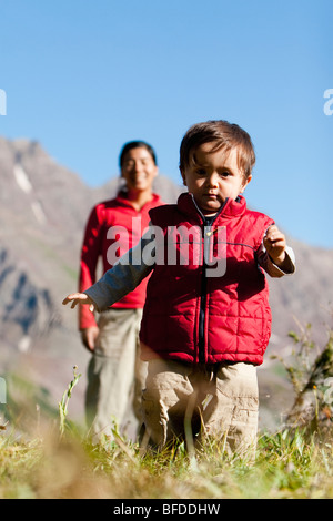 Mother watches 14 month old son explore meadow taking break on backpacking trip. Maroon Bells Snowmass Wilderness - Stock Photo