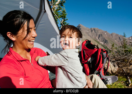 Mother watches 14 month old son play in meadow at camp. Backpacking trip Maroon Bells in Snowmass Wilderness outside - Stock Photo