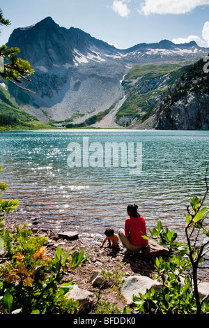 A mother & 14 month old son play on shore of Snowmass Lake (10,980ft) Maroon Bells in the Snowmass Wilderness just - Stock Photo